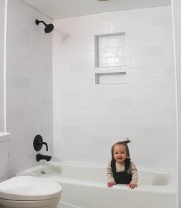 Cute baby sitting in a white, freshly tiled shower!