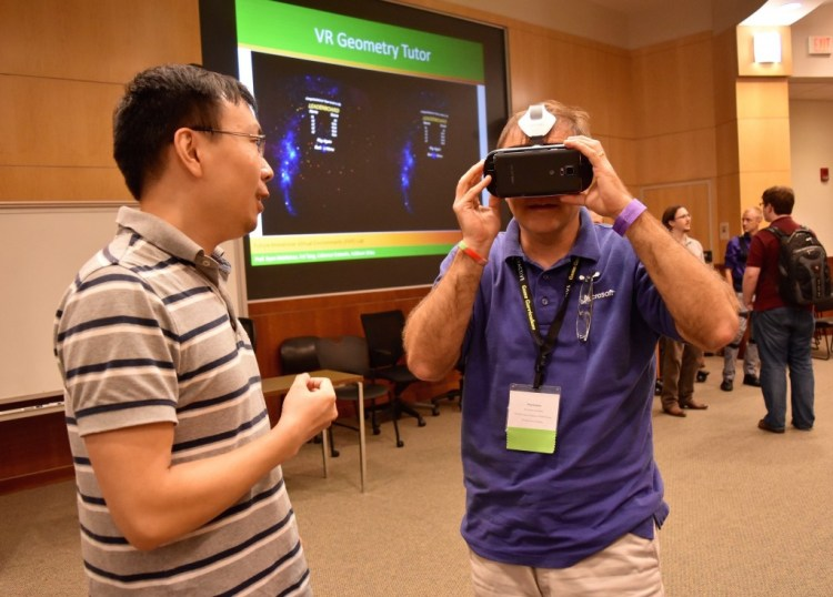 Fei Tang showing the teachers the mobile VR headset.