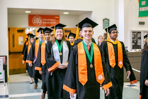 Isaac Urcuyo, Jessica Morgan, Deep Mistry and Michael McNew (from center, right to left) are all smiles during the procession into their graduation ceremony for the Erik Jonsson School of Engineering and Computer Science.