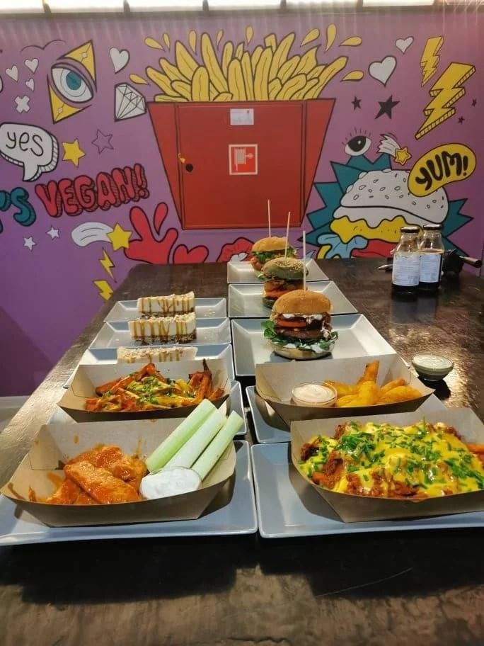 színes fal előtt street food ételek a pulton