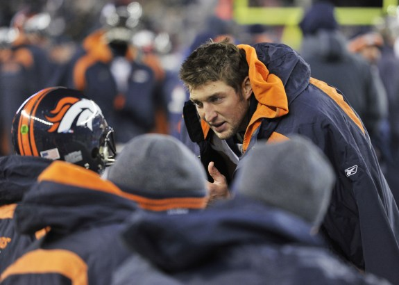 Denver Broncos Tim Tebow (15) talks with players in the bench area during fourth quarter action in the NFL AFC divisional playoff game against the New England Patriots January 14, 2012 at Gillette Stadium in Foxboro, MA. — Photo © Eric Lars Bakke/ Denver Broncos