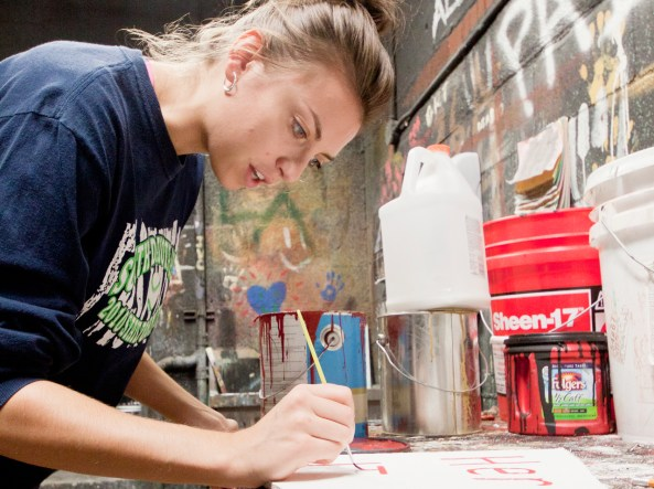 """Sarah Kingsbury, 21, senior of Winner, S.D., paints a sign Wednesday afternoon in Memorial Hall. Kingsbury is one of several students doing production and set work for the upcoming Theatre Department's """"Little Shop of Horrors"""" production. – Photo by T.J. Thomson"""