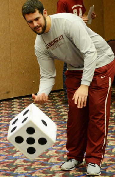 Austen Stevens, 23, resident director of Edna Hall, rolls the dice Saturday during the Life-size Clue event hosted in the Scottsbluff room in the Student Center. —Photo by Jordyn Hulinsky