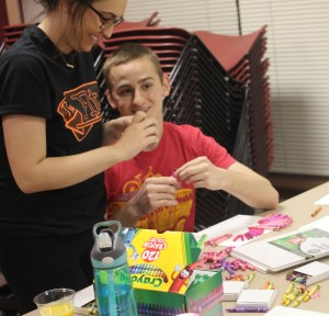 Savannah Hurtado, sophomore of Westminster, Colorado, left, and Evan Smith, sophomore of Gillette, Wyoming, unwrap crayons to complete a project during Craft Night at The Pit in the Student Center. --Photo by Shontell Roseberry