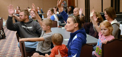 The Carpenter family raises their hands in response to a question Monday during the Oxfam Hunger Banquet in the Student Center Ballroom. —Photo by Alyssa Sanders