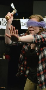 "Blindfolded Courtney Smith, freshman of Hampton, prepares to throw an axe at the audience Monday during play ""#1: Flights of Fancy"" as part of a dress rehearsal of ""Too Much Light Makes The BabyGo Blind,"" in the Black Box Theatre. —Photo by Jordyn Hulinsky"