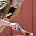 Kalli Feddersen, 20, junior of Laramie, Wyoming, paints a bench Saturday at the Dawes County Historical Society Museum during of The Big Event.— Photo by Jordyn Hulinsky