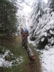 Nick and Maddie haul a large, heavy log uphill after dismantling it from a broken-down bridge on Conserve's grounds.