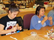 Hannah and SA make paper beads for a good cause
