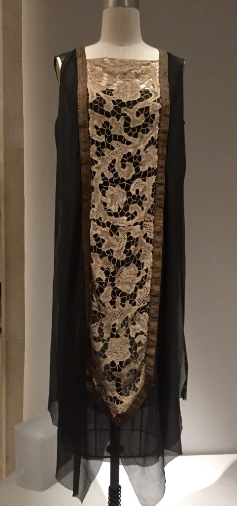 Manus x Machina - evening dress attributed to Callot Soeurs, ca. 1920, haute couture - hand and machine-sewn black silk chiffon with hand sewn inserts of antique ivory bobbin-made tape lace, hand-applied handmade gold metallic braided passementerie
