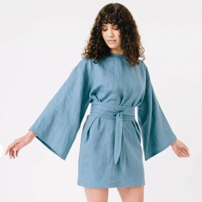 Image - woman wearing Array Top in blue fabric with flared sleeves, tunic length