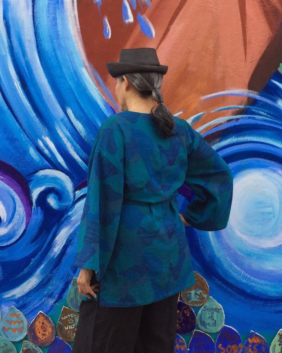 Asian woman standing in front of mural with back to camera - wearing blue tunic and black hat