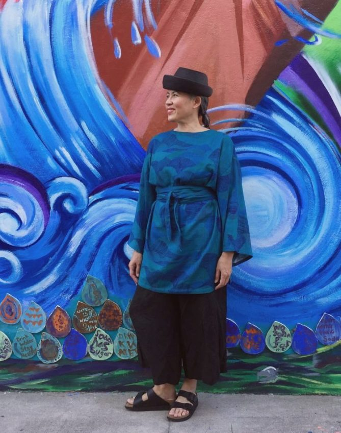 Asian woman in blue tunic and black pants standing in front of mural