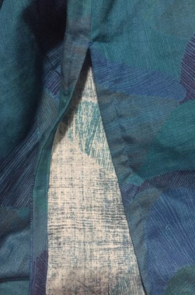 Close up view of vent at bottom of side seam of blue tunic