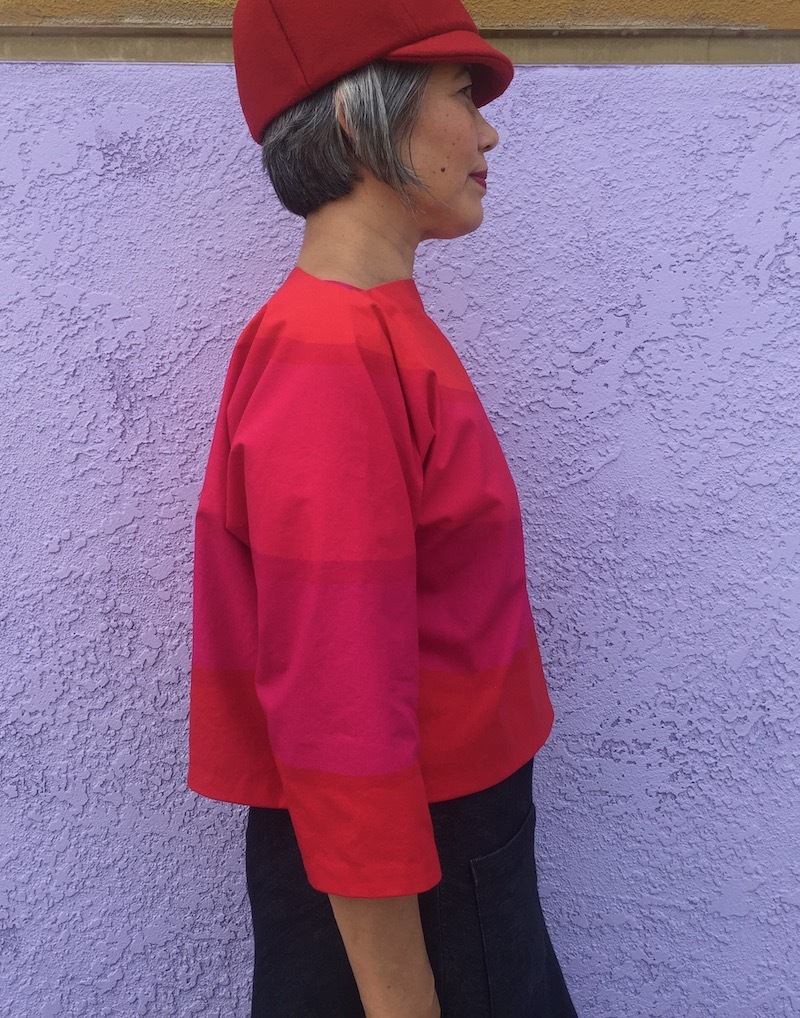 Asian woman facing right wearing red hat and Suri top in bright orange and hot pink.