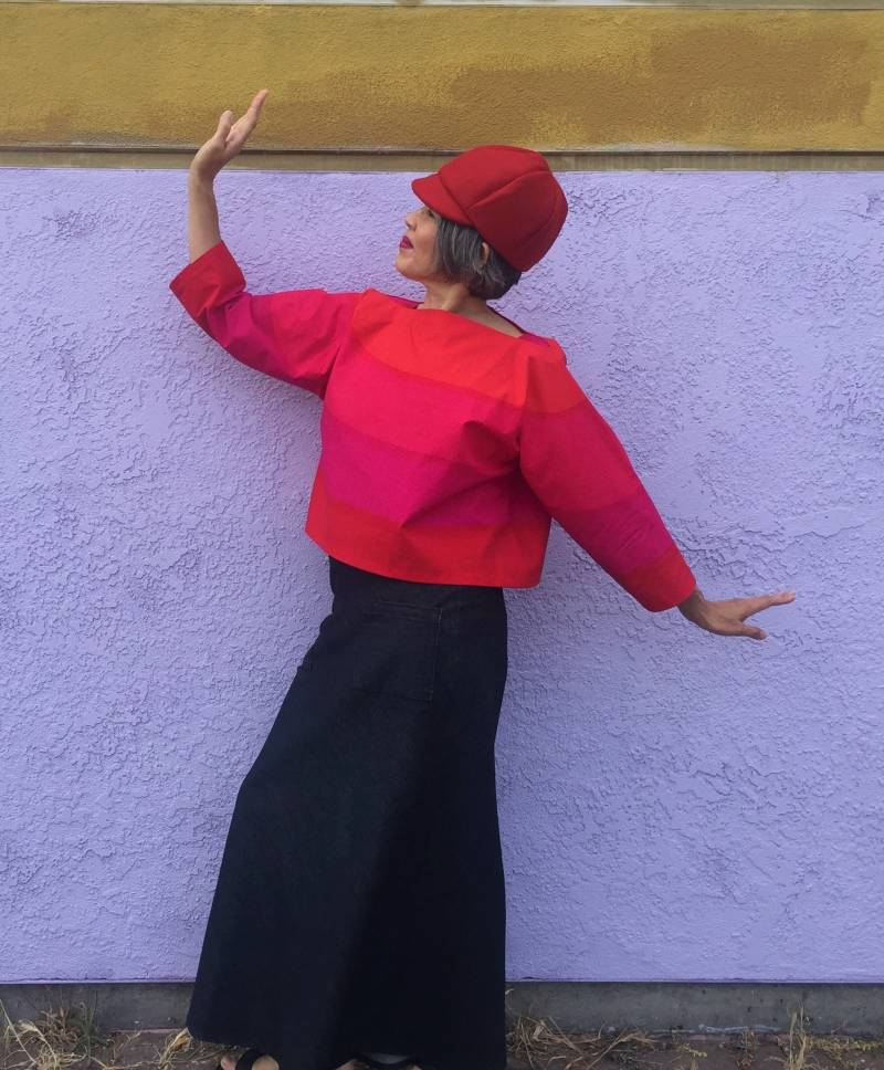Asian woman posing in front of white wall wearing red hat and top in bright orange and hot pink top and denim skirt.