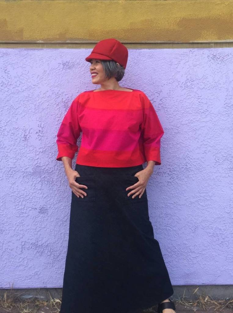 Asian woman standing with hands in pockets of demin skirt, wearing Suri top in bright orange and hot pink.