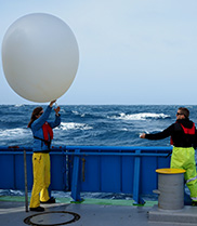 Two scientists deploy a weather balloon from the RV Investigator.