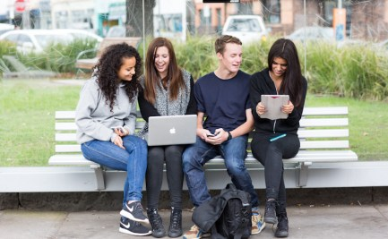 Group of young adults sitting at bus stop using a range of electronic devices.