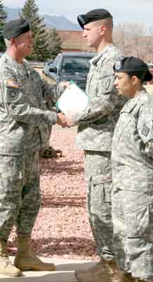 Maj. Gen. Mark A. Graham, commanding general, Division West (First Army) and Fort Carson, presents a Soldier with a certificate of reenlistment during a ceremony in front of the post headquarters March 17.