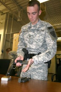 Sgt. Christopher Holland, 127th Military Police Company, loads his pistol Monday before his patrol shift begins.