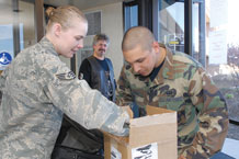 (Air Force photo by Rob Bussard)  Second Lt. Mark George, 21st Contracting Squadron (right), searches a box carried into building 350 by Staff Sgt. Nichole Piazzo, 21st  Space Wing command section, as part of his entry controller responsibilities during the operational readiness inspection April 10. Proper entry control procedures are critical to safeguarding Peterson Airmen and facilities during a crisis or exercise.