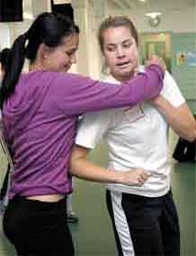 Cayley Wetzig, right, escapes a stranglehold from her sister, Casey Wetzig, during Fight Back 101 training.