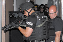 (Air Force photo by Larry Hulst) Local law enforcement officers prepare to enter a vacant Peterson dormitory room as part of a building search and clear exercise. Police from the Colorado Springs Police Department, El Paso County Sheriff, and the Federal Bureau of Investigation teamed with 21st Security Forces Squadron Airmen for a day of joint training. Peterson security forces Airmen and their civilian counterparts practiced a variety of policing skills including tactical team movements, search and clearing of rooms and buildings, hostage rescue operations, weapon tactics, rules of engagement and mission execution procedures.