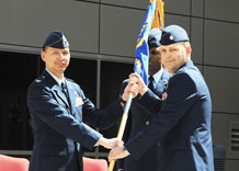 Lt. Col. Douglas Schiess, right, accepts the 4th Space Operations Squadron guidon from Col. Stanford Kekauoha, 50th Operations Group commander, during the 4th SOPS change-of-command ceremony in front of the DeKok building June 19. Colonel Schiess succeeded Lt. Col. Tommy Roberts, who will attend the Industrial College of the Armed Forces at Fort McNair in Washington, D.C.