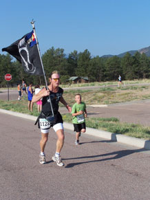 Pikes Peak Road Runner member Mike Olson, ran with the prisoner of war-missing in action flag at last year's Veterans' Home Run 5K run/1K walk. Olson was one of 300 particpants in last year's event. This year's event takes place June 27 at Air Academy High School.