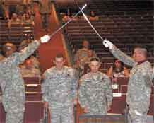 Sgt. 1st Class Justin Widhalm, second from left, walks with Sgt. Gavin Sibayan as he crosses the line of authority during the Warrior Transition Battalion's first noncommissioned officer induction ceremony June 24 at McMahon Auditorium.