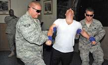 Tech. Sgt. Jerome Stanton (far left), 721st Security Forces Squadron noncommissioned officer in-charge of training, uses an X26E Taser to subdue Chaplain (Capt.) Ronald Feeser, 21st Space Wing chapel, in a training scenario while Airman 1st Class Ryan Higgins, 721st SFS, and Staff Sergeant Daniel Chase, 721st SFS support him for safety July 20. Chaplain Feeser volunteered to assist the 721st SFS by playing the role of a suspect. This local training complies with a new Air Force Security Force training directive to certify its Airmen in the proper application of Tasers. (Air Force photo by Roberta McDonald)