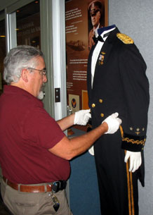 Paul Martin adjusts the tail coat on General Arnold's formal evening dress uniform in the recently completed Arnold Hall exhibit.