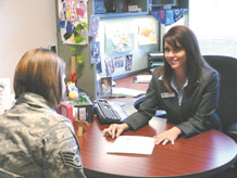 Lisa Ballard, 21st Space Wing military child education coordinator, meets with a customer at her office in the Airmen & Family Readiness Center. The position of military child education coordinator was specifically designed to assist Airmen by enhancing the educational experience of their children. (Air Force photo by Tech. Sgt. Stacy Oliver)