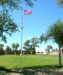 """A """"crow's nest"""" flag pole is in the plaza at Fort Garland. The fort's adobe buildings surround the plaza."""