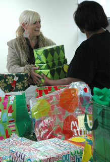 """Ms. Windy Torgerson, 2nd Space Operations Squadron hands gifts donated by Schriever particpants over to El Paso County Human Services case worker Tamella Pierce Dec. 15 at the El Paso County Human Services building. 2nd SOPS representatives led a base-wide effort to collect Christmas gifts for 101 children in protective services as part of the """"Christmas for Kids"""" program."""