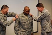 Lt. Gen. Mike Gould and Chief Master Sgt. Todd Salzman pin stripes on a surprised Master Sgt. Bryant Ward in the commandant's conference room Dec. 22. Photo by Staff Sgt. Don Branum