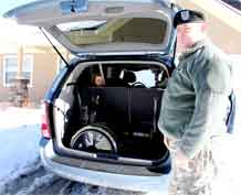 Sgt. Robert McPherson, 361st Aviation Detachment, 1st Battalion, 2nd Aviation Regiment, 2nd Infantry Division, shows how his daughter, Tiffany's, wheelchair fits in the van they received as part of Operation Once in a Lifetime's Heroic 7 Wishes.