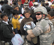 Vice President of the Rising Four Club, Senior Airman Robert Evans, 506th Expeditionary Operation Support Squadron Airfield Management, hands out soccer balls and school supplies to local children during Operation Soccer Ball Jan. 5, 2010. Operation Soccer Ball was a humanitarian effort sponsored by the Kirkuk Regional Air Base's Rising Four Club. Airman Thomas is a native of Austin, Texas, and is deployed from the 21st Comptroller Squadron, Peterson AFB, Colo. (U.S. Air Force photo/courtesy photo)