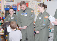 Capt. Chris Smyder receives 'thank you' letters by a student at Trailblazer Elementary School Jan. 29 while Airman 1st Class Meagan Pool and 2nd Lt. Laura Simmons look on. The Airmen painted a replica of the United States on the school's playground and were presented with 'thank you' letters from the students. The Airmen also took the opportunity to visit classrooms, talk about being an Airman and the importance of education. (U.S. Air Force photo/Staff Sgt. Daniel Martinez)