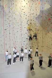Soldiers from the Warrior Transition Unit climb up on the rock wall as others await their turn.