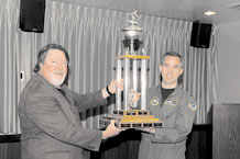 Warren Schroeder, 21st Force Support Squadron marketing, and Col. Stephen N. Whiting, 21st Space Wing commander, hoist the SnoFest Commander's Cup, Feb. 3, in the wing conference room. Peterson skiers won the cup posting a combined time of 83.18 seconds in racing Jan. 29 at Keystone Resort. (U.S. Air Force photo/Roberta McDonald)