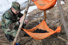Cadet 1st Class Talon Pope sets up a three-tiered water filtration system. Photos by Rachel Boettcher