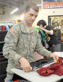 Photo by Spc. April York.  Spc. Zackery Guerrero, armor crewman, Headquarters and Headquarters Detachment, 2nd Battalion, 8th Infantry Regiment, 2nd Brigade Combat Team, 4th Infantry Division, folds clothes at a local Goodwill store. Guerrero and other Soldiers in his unit volunteer at different organizations around the Colorado Springs area.