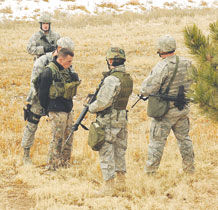 During the 21st Space Wing Condor Crest exercise, 21st Security Forces Squadron Airmen detain a shooting suspect (left) Feb. 25 in the wooded area behind the Peterson Shoppette. The active shooting scenario was part of the wing's quarterly exercise. In this scenario, the gunman fired into a crowd of Airmen and civilians who had just evacuated Air Force Space Headquarters Building 1, near the north gate. The gunman was tackled and then removed from the parking lot to the wooded area by security forces. Condor Crest exercises also help ensure the 21st SW is able to complete its mission of professionally operating, supporting and protecting its personnel and resources during actual incidents. (U.S. Air Force photo/Roberta McDonald)
