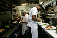 Lead Cook Jose Romero (left) prepares an order of Cajun shrimp for The Red Door as Sous Chef Jermaine Spotwood plates a steak dish for The Wellington Steak & Martini Lounge. The kitchen works for both of the restaurants, in Mission Hills. Photo by David Brooks