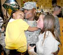 Sgt. James Copeland kisses his daughter, Jasmine, as his wife, Jessica, looks on during the welcome home ceremony for the 32nd Transportation Company held at the Special Events Center Monday.