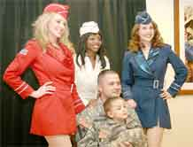 From left, New York City-based Liberty Bells Natalie Loftin Bell, Melissa Vanpelt Johnson and Nancy Emerson pose for a photo with Staff Sgt. John Dornstadter, 110th Military Police Company, 759th Military Police Battalion, and his son Joseph, 4, Monday at Fort Carson USO.