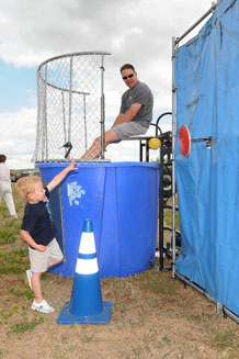 Barrett Giger takes a try at dunking Chief Master Sgt. Todd Salzman, Academy command chief, during the base picnic. Photo by Rachel Boettcher