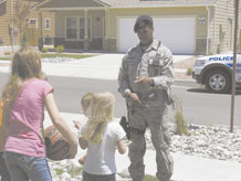 Senior Airman R. Jamal Guichon, 21st Security Forces Squadron, stops to talk with Peterson Air Force Base housing residents June 15. Residents have likely noticed an increased presence of security forces. The new neighborhood patrols are part of the 21st SFS integrated defense plan which calls for security forces to be more visible on base. (U.S. Air Force photo/Monica Mendoza)